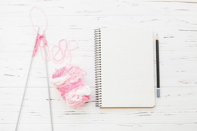 Tejer; hilo; bloc de notas y lápiz sobre fondo de madera