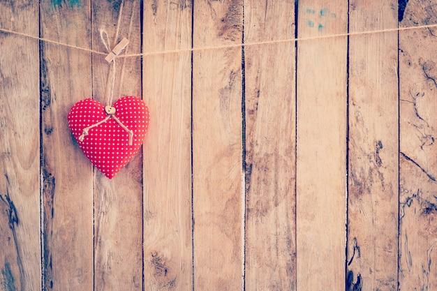 Tejido de corazón colgando de tendedero y fondo de madera con espacio.
