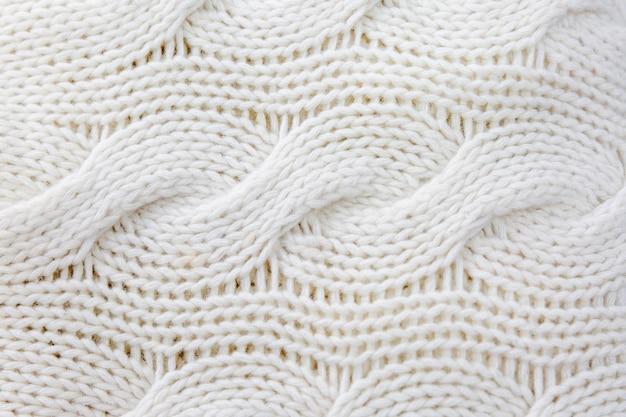 Tejido de lana blanca con trenzas. de cerca. antecedentes. espacio para texto. hobby y artesanía.