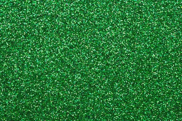 Tejido de lentejuelas brillantes. textura verde brillante, fondo oscuro brillo. superficie brillante de textil