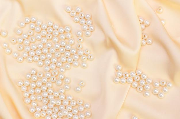 Tejido de lujo abstracto con perlas. tejido de seda natural. textura de tela de seda de color beige dorado con perlas.