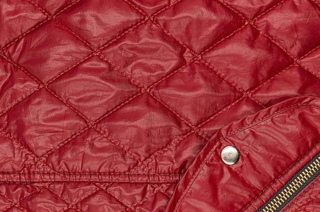 Tejido mortadela rojo con rombos de costura y bolsillo con botón y cremallera.