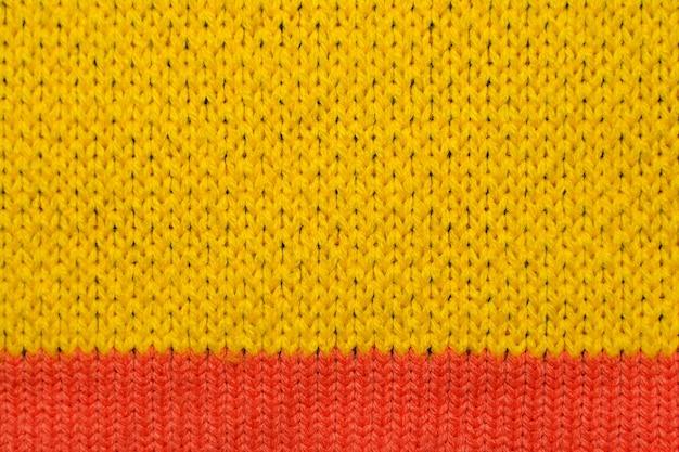 Tejido de punto sintético amarillo y rojo de cerca. textura de tejido de punto. antecedentes