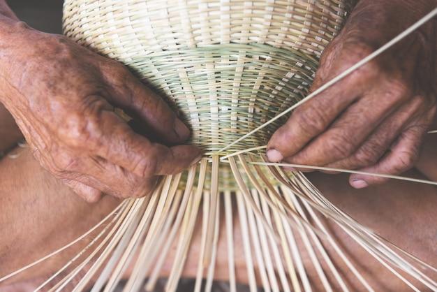 Tejiendo cesta de bambú de madera, mano de hombre mayor de edad trabajando artesanías hechas a mano cesta para producto de la naturaleza en asia