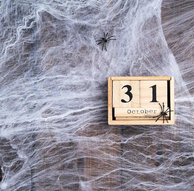 Tela de araña blanca y calendario retro de madera hecho de bloques con la fecha del 31 de octubre