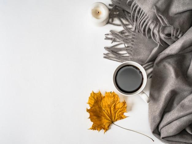 Tela escocesa gris cálida, taza blanca con café negro, una vela blanca y hoja amarilla de otoño. humor de otoño vista superior. copyspace