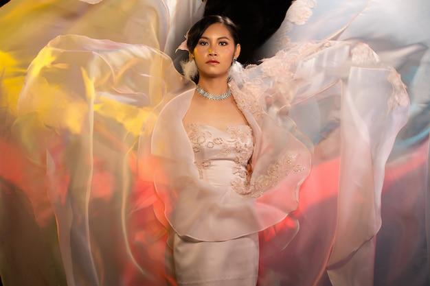 La tela de la falda ondeante de la mujer transgénero de asia usa un vestido largo de noche hermoso, arroja la ropa al aire y sonríe a la cámara sobre las luces de fondo coloridas, espacio de copia de iluminación de estudio