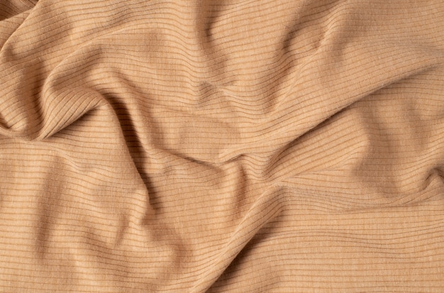 Tela de jersey de algodón beige simple arrugada desde arriba.