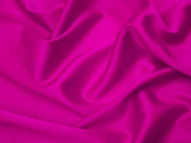 La tela rosa se presenta con ondas. tela de seda rosa para el fondo o la textura.