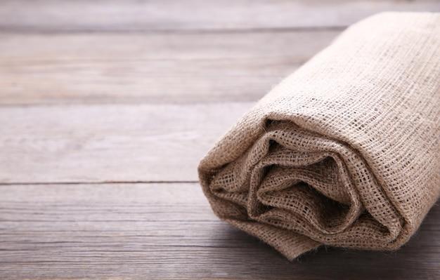 Tela de saco enrollada sobre fondo de madera gris