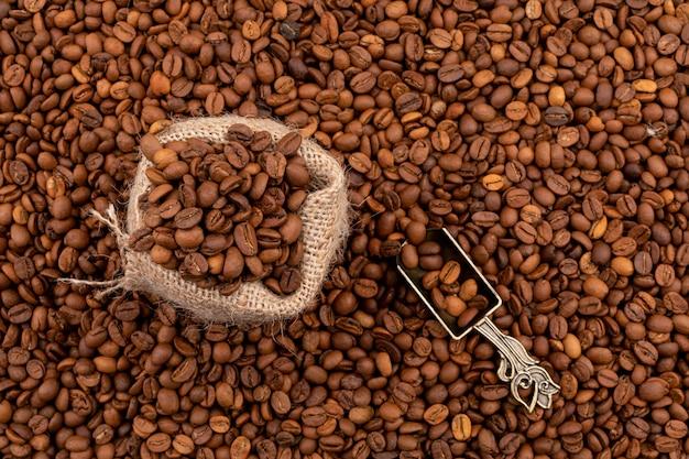 Tela de saco llena de granos de café en la superficie de los granos de café