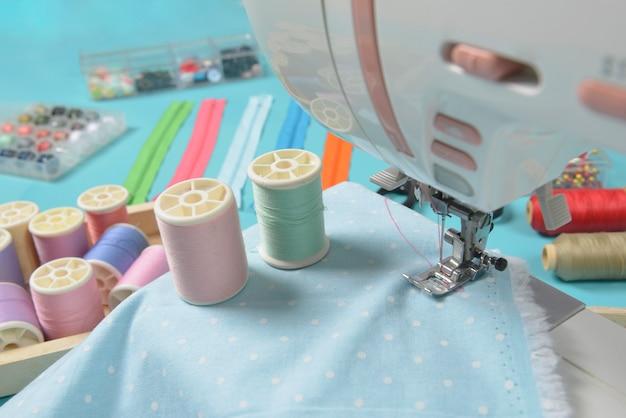 Telas en máquina de coser en medio de las tijeras, botones de camisa, cremallera, pin y rollos de hilo.