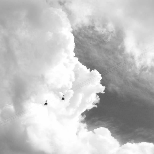 Teleférico con hermosas nubes impresionantes en blanco y negro