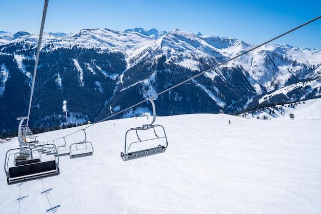 Teleférico del remonte sobre las hermosas montañas cubiertas de nieve