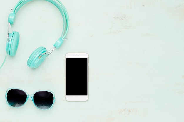 Teléfono y accesorios de verano sobre fondo claro.