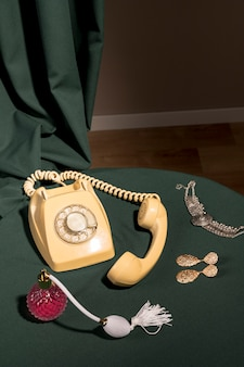 Teléfono amarillo junto a artículos femeninos.