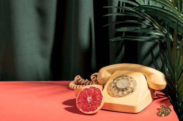 Telefono amarillo junto a pomelo sobre mesa.
