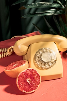 Teléfono amarillo vintage junto a pomelo a la mitad