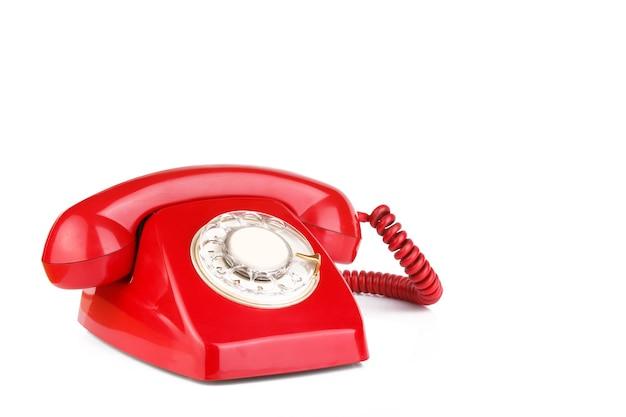 Teléfono antiguo en color rojo aislado sobre superficie blanca
