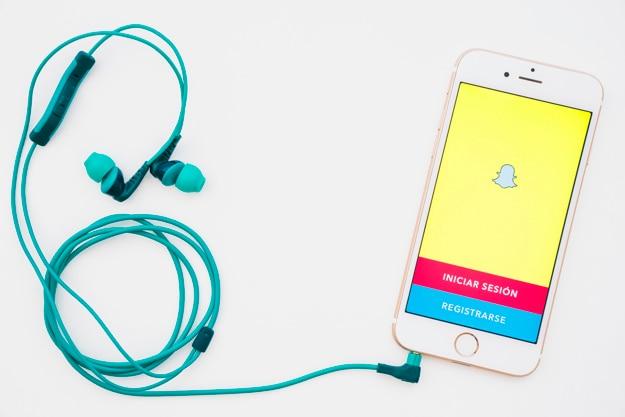 Teléfono con la aplicación de snapchat y auriculares