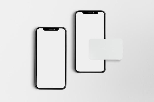 Teléfono blanco en blanco y tarjeta de visita sobre fondo blanco.