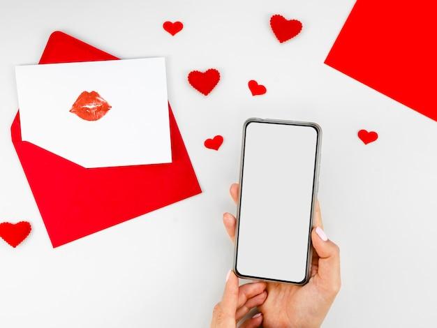 Teléfono en blanco junto a la carta de amor