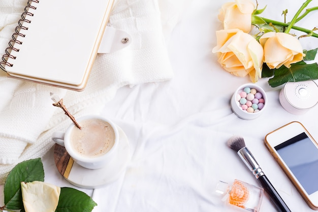 Teléfono, blanco taza de café y rosas con cuaderno en cama blanca y cuadros, acogedora luz de la mañana.