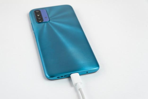 Teléfono celular azul conectado a cable usb tipo c - cargando Foto gratis