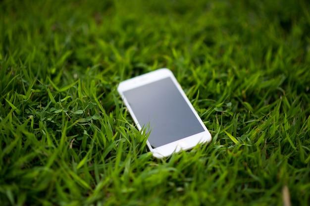 Teléfono celular colocado en una hierba verde claro