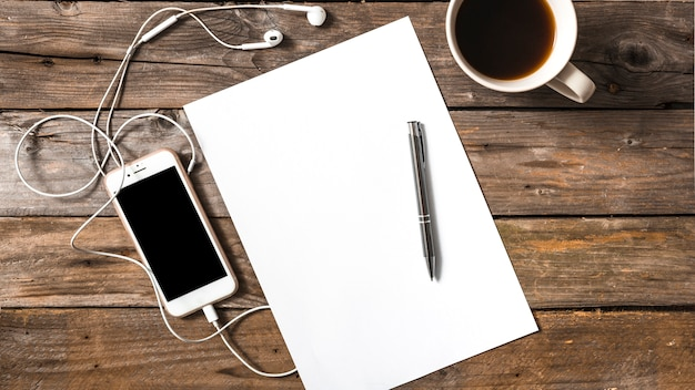 Teléfono celular conectado con auriculares; bolígrafo; taza de papel y café sobre fondo de madera