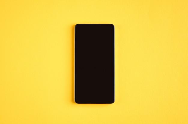 Teléfono celular negro en superficie amarilla, teléfono móvil.