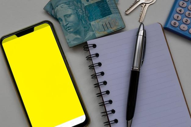 Teléfono celular con pantalla amarilla, lápiz de libreta, calculadora y moneda brasileña control financiero
