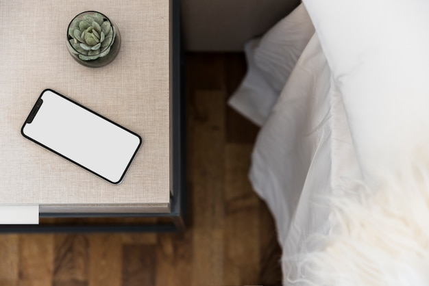 Teléfono celular de pantalla blanca y planta de cactus en mesa auxiliar.