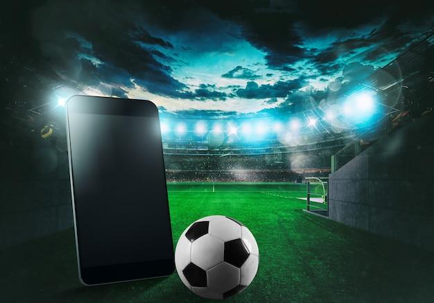 Teléfono celular y pelota con un estadio de fútbol al fondo