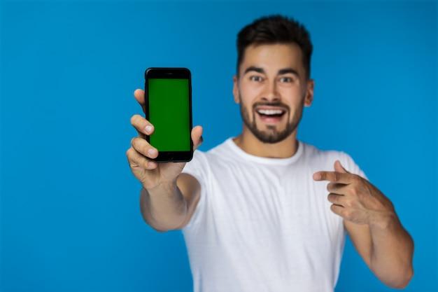 Teléfono celular en primer plano y joven guapo en el fondo