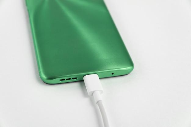 Teléfono celular verde conectado al cable usb tipo c - cargando
