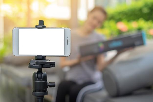 El teléfono elegante de la pantalla en blanco en mujer de negocios del dueño del tiroteo del trípode trabaja en casa