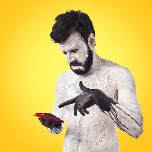 Teléfono de la explotación agrícola del monstruo en fondo colorido