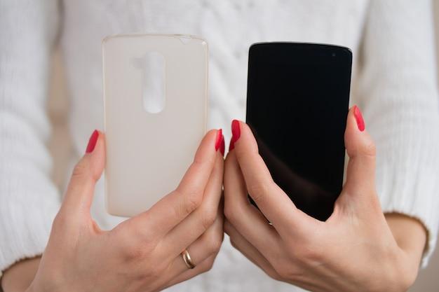 El teléfono y la funda para el teléfono en manos femeninas.