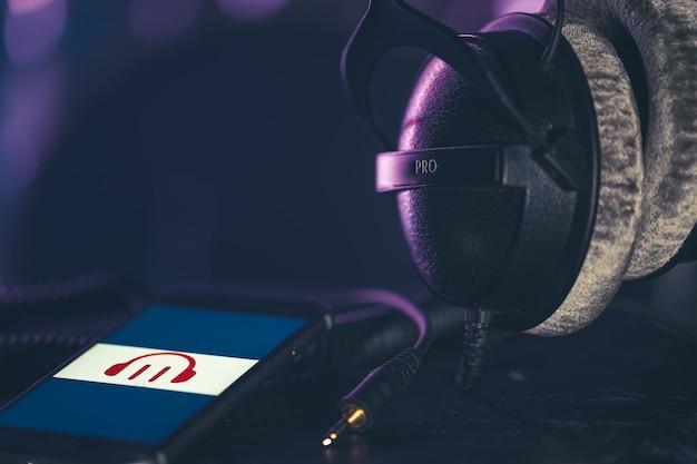 Teléfono con icono de música y auriculares sobre fondo borroso, concepto de escucha de música, espacio de copia.