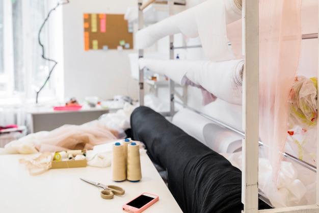 Teléfono inteligente y accesorios de costura en el banco de trabajo