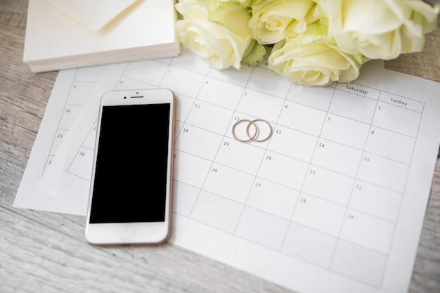 Teléfono inteligente; anillos de boda; sobre y rosas en el calendario sobre el tablón de madera.