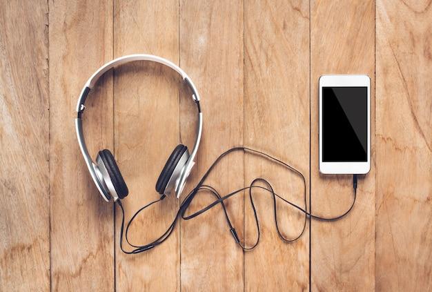 Teléfono inteligente y auriculares en la mesa