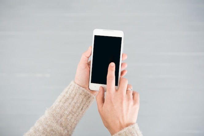 Teléfono inteligente blanco en manos femeninas sobre un fondo gris