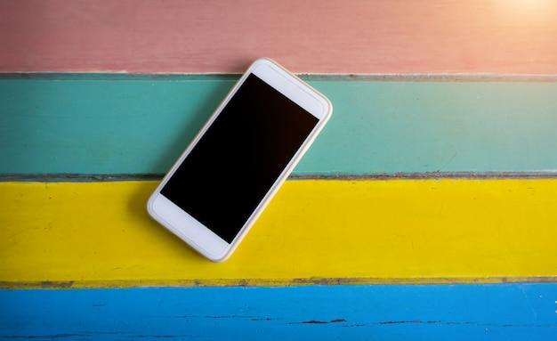 Teléfono inteligente blanco con pantalla en blanco sobre mesa de madera colorida
