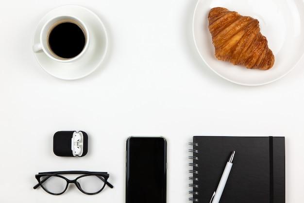 Teléfono inteligente, café, cuaderno, bolígrafo, croissant, gafas y auriculares en el estuche