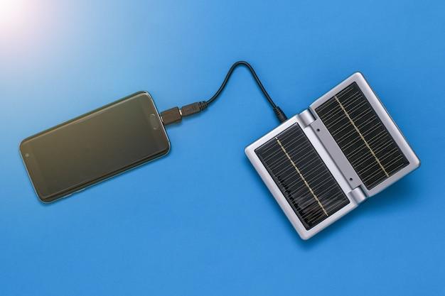 El teléfono inteligente se carga desde un dispositivo con paneles solares. uso de energía solar. tecnología del futuro.