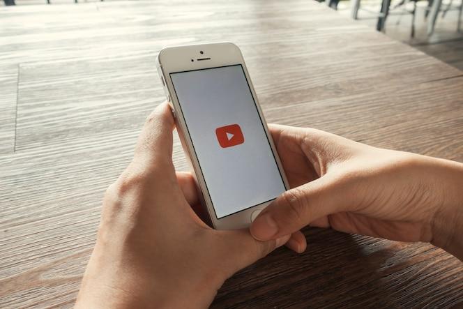 Teléfono inteligente con la aplicación de youtube en la pantalla que miente en el escritorio de madera viejo