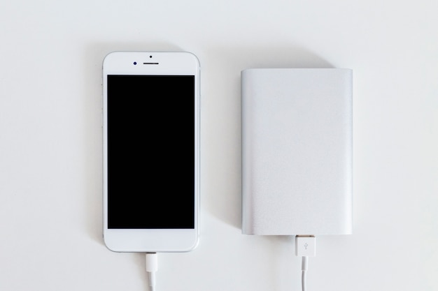 Teléfono inteligente conectado con el cargador del banco de potencia sobre el fondo blanco
