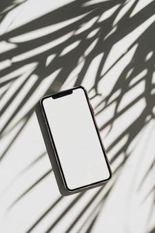 Teléfono inteligente con copia espacio maqueta pantalla sobre fondo blanco con sombra de hojas de palma